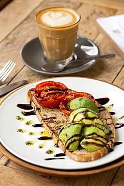 High angle close up of tomato and avocado bruschetta with balsamic vinegar reduction in a cafe - 1174-8202