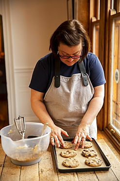 Woman wearing glasses and apron standing at wooden table, baking chocolate chip cookies