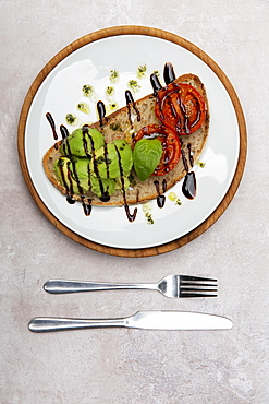 High angle close up of tomato and avocado bruschetta with balsamic vinegar reduction in a cafe - 1174-8228