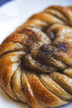 A platted glazed fresh baked cinnamon bun