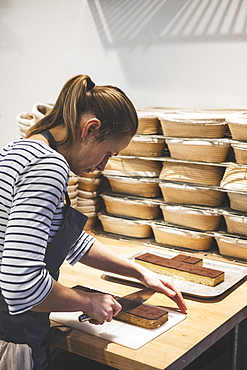 A specialist bakery, a baker cutting sections of millionaire's shortbread with a large knife