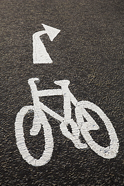 High angle close up of white bicycle lane sign on concrete path