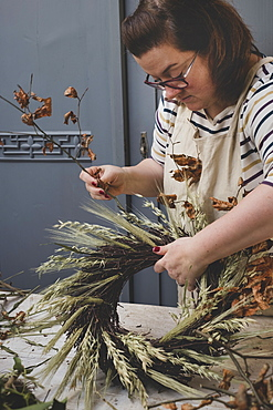 Woman making a winter wreath, adding dried grasses and seedheads and twigs with brown leaves