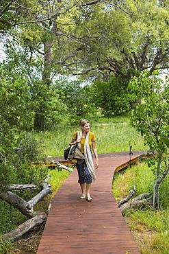 adult woman walking wooden path, tented camp, Botswana