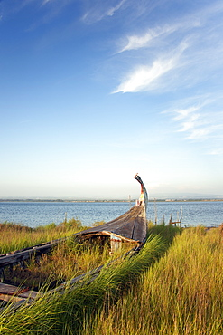 An abandoned wooden moliceiros fishing boat on the dunes overlooking the sea, Ria de Aveiro Lagoon, Portugal