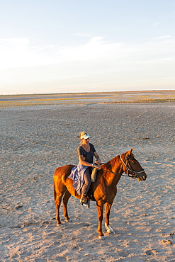 A woman on horseback at sunset in open space