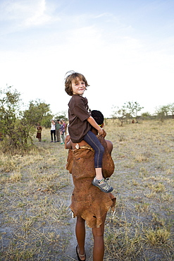 Five year old boy riding on shoulders of a San bushman