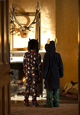 Rear view of two children wearing pyjamas, towelling robe and hats standing in front of a fireplace, hunting trophy on wall