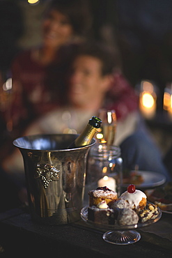 Close up of champagne bottle in metal wine cooler, glass cake stand with selection of cakes, person in the background