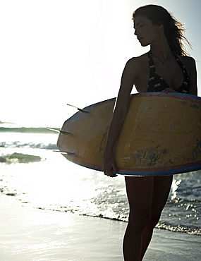 Woman standing on a sandy beach by the ocean, holding a surfboard