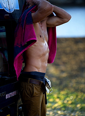 Side view of shirtless man leaning against a van, drying himself with pink towel, Cornwall, United Kingdom