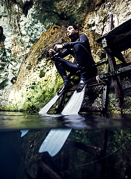 Man wearing wet suit and flippers sitting on a platform, rocks in background, United States of America