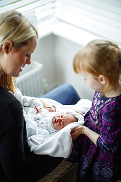 Mother and daughter caring for newborn baby