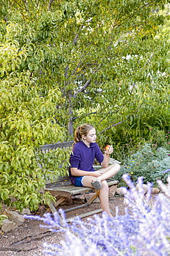 11 year old girl sitting on bench reading a book