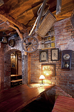 Bar with exposed brickwork and cart wheel, basket and old photographs at night, Estonia