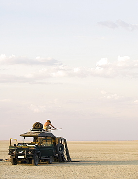 Man standing on top of 4x4 parked on the Makadikadi Salt Pans in Botswana