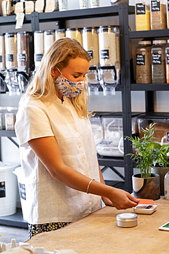 Woman wearing face mask shopping in a local store, making contactless payment, Watlington, Oxfordshire, United Kingdom