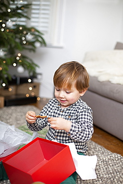 Young boy sitting on living room floor, unwrapping Christmas present in red box
