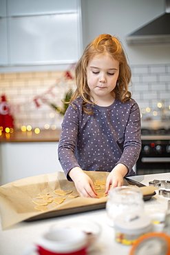 Girl standing in kitchen, baking Christmas cookies