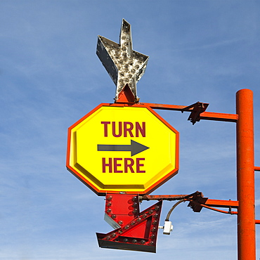 Turn Here, yellow traffic sign with arrow, on a gantry with a silver star shape, United States of America