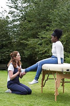 Therapist touching a client's feet, an outdoor therapy session