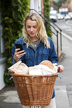 Young blond woman on bicycle with basket, checking her mobile phone, Oxfordshire, England, United Kingdom
