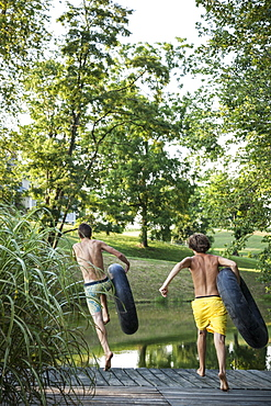 Two boys, leaping from the jetty into the water holding swim floats, Maryland, USA