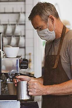 Male barista wearing brown apron and face mask working in a cafe, frothing milk