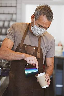 Male barista wearing brown apron and face mask working in a cafe, pouring coffee
