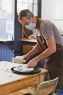 Waiter wearing brown apron and face mask working in a cafe, clearing table