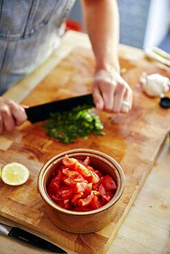 Chopping basil for tomato salad
