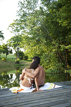 A young couple, boy and girl, sitting close together on a wooden jetty by a water pool, Maryland, USA