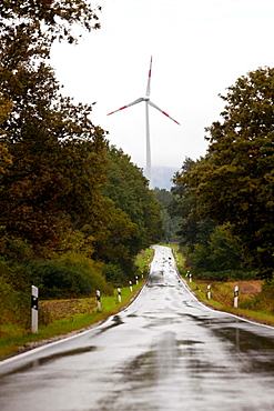 Wind turbine and wet straight road nr Trier, in the Moselle wine region, Germany