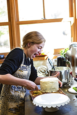 Teenage girl in kitchen applying icing to cake