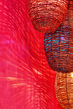 Wicker light fixtures casting shadows on red wall