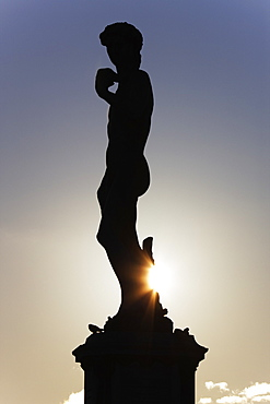 Silhouette of classical statue with setting sun behind
