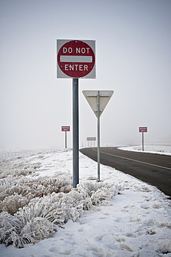 Road signs on road in wintry landscape
