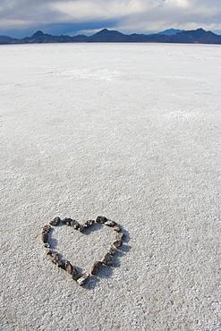 Pebbles arranged on salt flat in the shape of a heart