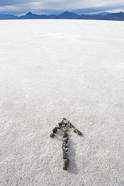 Pebbles arranged on salt flat in the shape of an arrow