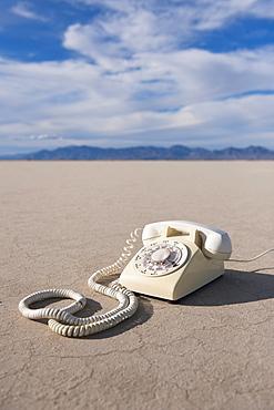 Vintage telephone on salt flat