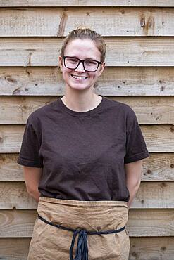 Portrait of female barista with blond hair and glasses, leaning against wall on a break