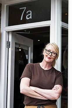 Portrait of waitress with blond hair and glasses, leaning against entrance door, smiling at camera.