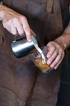 Close up of barista wearing brown apron pouring cafe latte.