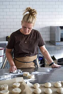 Blond woman wearing brown apron standing in a kitchen, baking danish pastries.