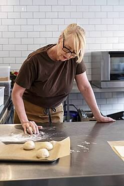 Woman in brown apron standing in a cafe kitchen, mixing baking danish pastry dough