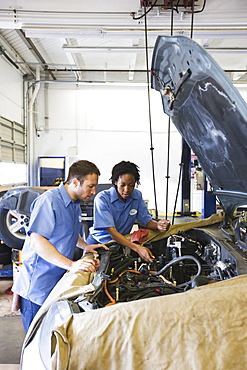 Male and female mechanics talk as they look at engine in auto repair shop