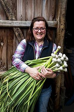 Smiling woman holding bunch of freshly picked garlic, Oxfordshire, United Kingdom
