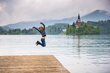 Woman jumping for joy, Lake Bled, Julian Alps, Gorenjska, Slovenia, Europe