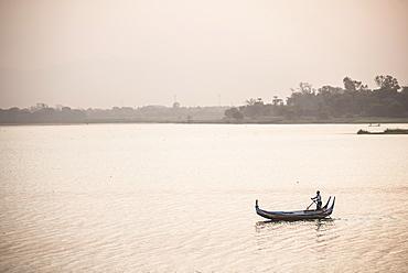 Rowing boat on Taungthaman Lake at sunrise, at U Bein Bridge, Mandalay, Mandalay Region, Myanmar (Burma), Asia