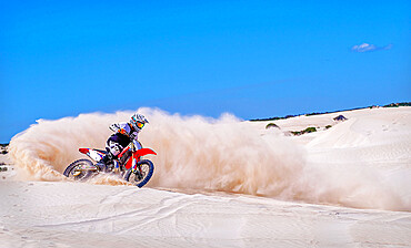 Trial bike rider kicking up sand at the sand dunes of Lancelin.